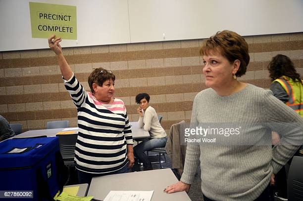 Beverly 'Jeannie' McCreery of Brandon Township raises a sign to indicate completion of recounting presidential ballots after a federal judge ordered...