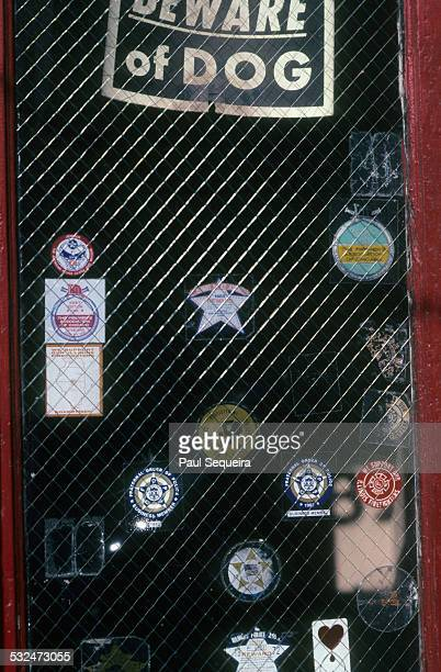 A 'Beware of Dog' sign is displayed on a reinforced glass door pane that contains several stickers supporting local police and fire deparments...