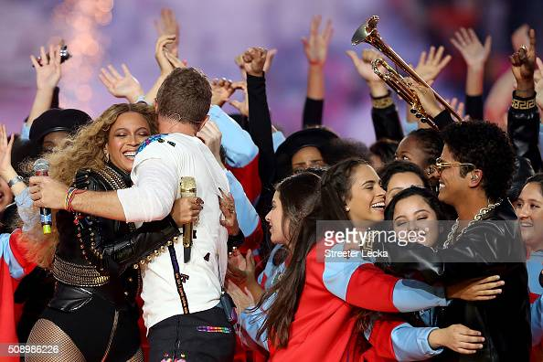 Beyonce hugs Chris Martin of Coldplay while Bruno Mars hugs fans following the Pepsi Super Bowl 50 Halftime Show at Levi's Stadium on February 7 2016...
