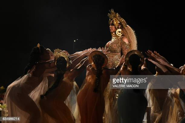 TOPSHOT Beyonce performs as she is pregnant with twins during the 59th Annual Grammy music Awards on February 12 in Los Angeles California / AFP /...