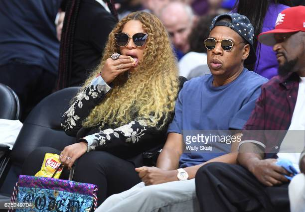 Beyonce snacks on potato chips as Jay Z looks on druing in Game 7 of the of the first round of the NBA Western Conference playoffs at the Staples...