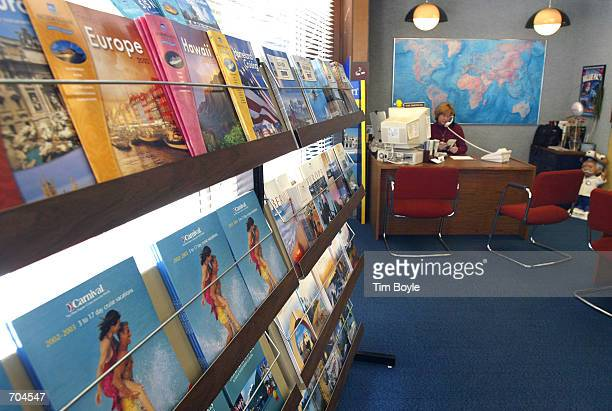 Beyond a wall of travel brochures manager and travel consultant Kim Sherwan speaks with a client on the phone while seated at her desk in front of a...