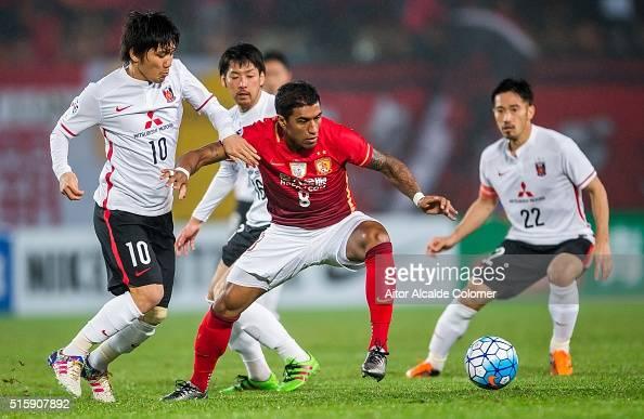 Bezerra Maciel Junior of Guangzhou Evergrande competes for the ball with Kashiwagi Yosuke of Urawa Red Diamonds and Abe Yuki of Urawa Red Diamonds...
