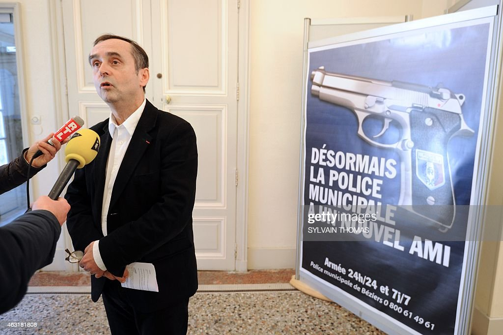 Beziers mayor <a gi-track='captionPersonalityLinkClicked' href=/galleries/search?phrase=Robert+Menard&family=editorial&specificpeople=554783 ng-click='$event.stopPropagation()'>Robert Menard</a> addresses reporters on February 11, 2015 next to a municipality campaign poster showing an automatic 7.65 handgun, with campaign slogans reading : 'From now on, the Municipal Police has a new friend', and 'Armed 24 hours a day, 7 days a week'. Since February 1st, the Beziers municipal police is equipped with lethal weapons, in this case automatic 7.65 handguns, and nine armed police officers already patrol the streets, mostly at night, of the town whose far-right party National Front-backed mayor <a gi-track='captionPersonalityLinkClicked' href=/galleries/search?phrase=Robert+Menard&family=editorial&specificpeople=554783 ng-click='$event.stopPropagation()'>Robert Menard</a> was elected last year.