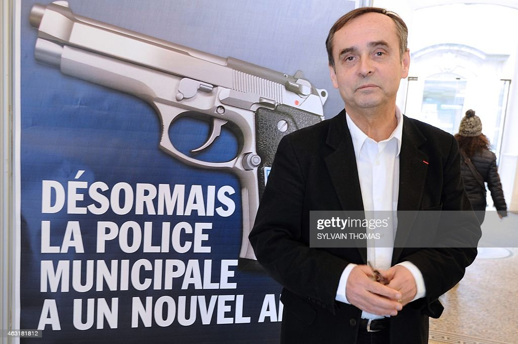 Beziers mayor <a gi-track='captionPersonalityLinkClicked' href=/galleries/search?phrase=Robert+Menard&family=editorial&specificpeople=554783 ng-click='$event.stopPropagation()'>Robert Menard</a> poses on February 11, 2015 in front of a municipality campaign poster showing an automatic 7.65 handgun, with a campaign slogans reading : 'From now on, the Municipal Police has a new friend'. Since February 1, the Beziers municipal police is equipped with lethal weapons, in this case automatic 7.65 handguns, as nine armed police officers already patrol the streets, mostly at night, of the town whose far-right party National Front-backed mayor <a gi-track='captionPersonalityLinkClicked' href=/galleries/search?phrase=Robert+Menard&family=editorial&specificpeople=554783 ng-click='$event.stopPropagation()'>Robert Menard</a> was elected last year.