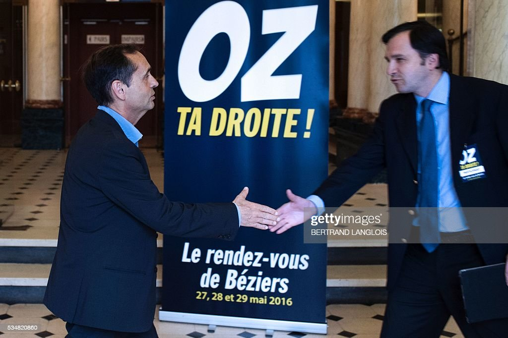 Beziers' mayor Robert Menard (L) shakes hands with a supporter at the municipal theatre in Beziers, southern France, on May 28, 2016 during 'Le Rendez-vous de Beziers' political meeting. Menard launched his own political movement 'Oz ta Droite'. / AFP / BERTRAND