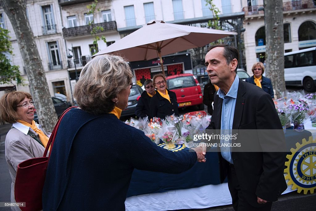 Beziers' mayor Robert Menard (R) shakes hands with an inhabitant in Beziers, southern France, on May 28, 2016 during 'Le Rendez-vous de Beziers' political meeting. Menard launched his own political movement 'Oz ta Droite'. / AFP / BERTRAND