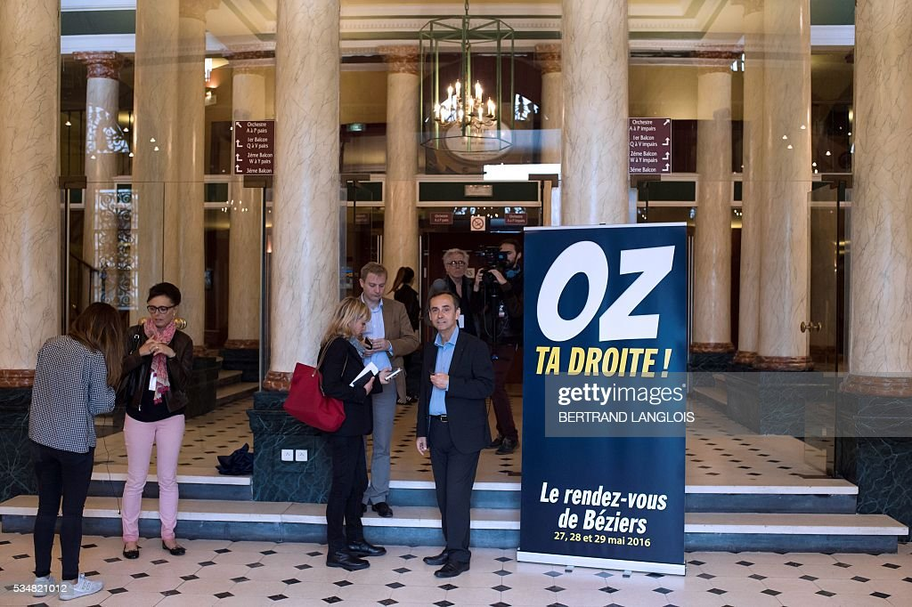 Beziers' mayor Robert Menard (C) stands at the entrance of the municipal theatre in Beziers, southern France, on May 28, 2016 during 'Le Rendez-vous de Beziers' political meeting. Menard launched his own political movement 'Oz ta Droite'. / AFP / BERTRAND