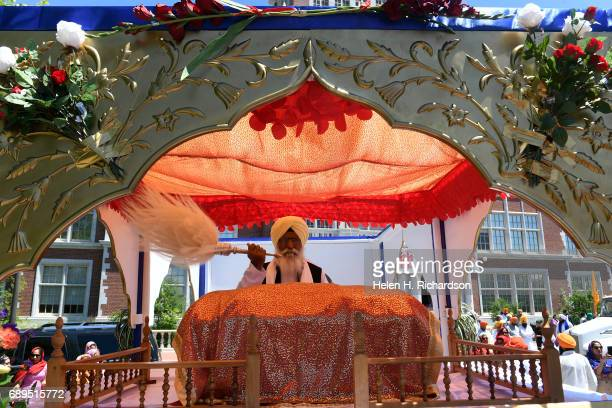 Bhai Avtar Singh a Sikh holy man waves feathers over the Guru Granth Sahib the Sikh holy book during the Vaisakhi ceremony outside of East High...
