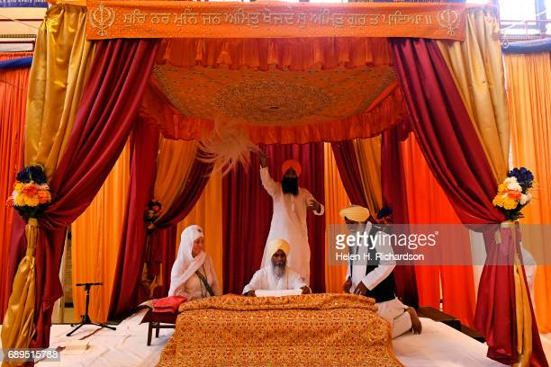 Bhai Avtar Singh seated in the middle a Sikh holy man puts fabric onto the Guru Granth Sahib the Sikh holy book during the Vaisakhi ceremony inside...