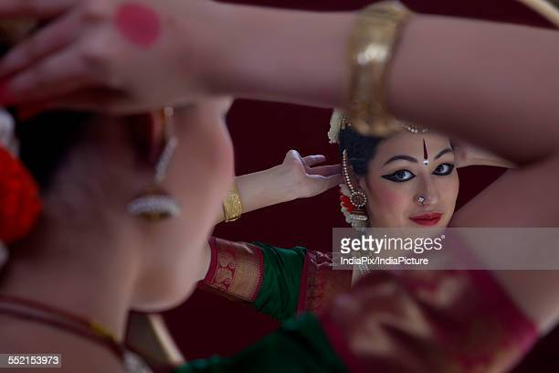 Bharatanatyam dancer getting dressed in front of mirror over black background