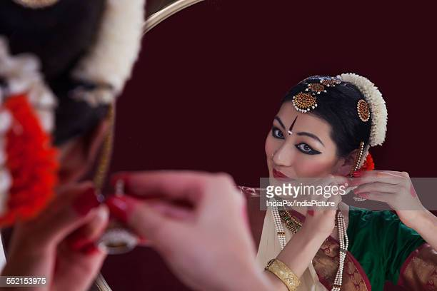Bharatanatyam dancer wearing earring in front of mirror over black background