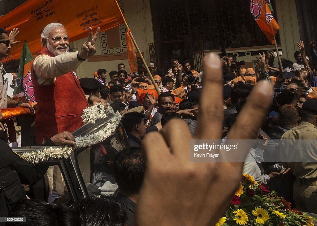 Bharatiya Janata Party (BJP) leader Narendra Modi gestures to supporters as he rides in an open jeep on his way to file nomination papers on April 9, 2014 in Vadodra, India. India is in the midst of a nine-phase election from April 7-May 12.