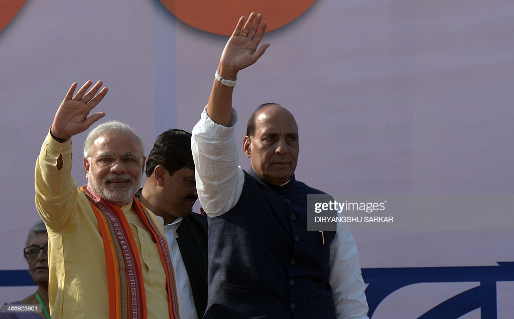 Bharatiya Janata Party (BJP) prime ministerial candidate and India's Gujarat state Chief Minister Narendra Modi (L) and BJP president Rajnath Singh (R) wave to supporters during a mass rally in Kolkata on February 5, 2014. Modi, tipped in opinion polls to be India's next premier, remains a polarising figure accused by critics of turning a blind eye to anti-Muslim riots in Gujarat in 2002 in which as many as 2,000 died. He has denied any wrongdoing. AFP PHOTO/Dibyangshu SARKAR