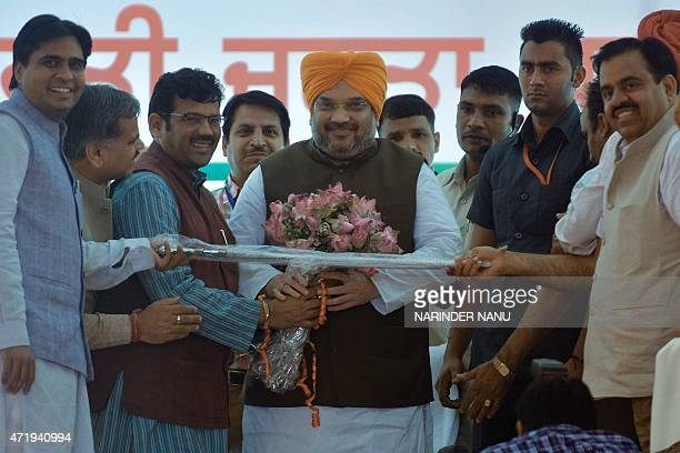Bharatiya Janata Party Punjab President Kamal Sharma Punjab BJP general secretary Tarun Chugh present flowers and a sword to the BJP chief Amit Shah...