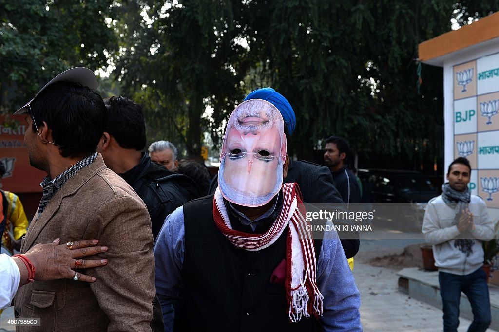 A Bharatiya Janata Party supporter is pictured wearing an upsidedown mask bearing the portrait of Indian Prime Minister Narendra Modi as they...