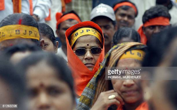 Bharatiya Janata Party supporter wearing a party headband featuring the party symbolthe lotus flower listens to her leader and former Indian union...