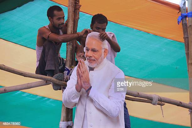 Bharatiya Janata Party supporters hold a cutout of Indian prime minister Narendra Modi as Modi addresses the 'Parivartan' rally in Gaya on August 9...