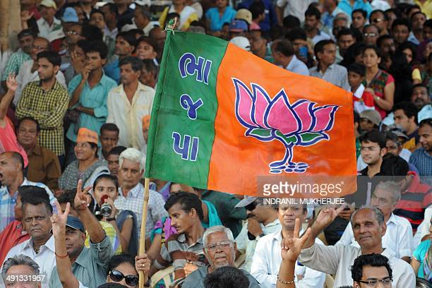Bharatiya Janata Party supporters wave a flag during a public rally by BJP prime ministerial candidate Narendra Modi after his victory in Vadodara on...