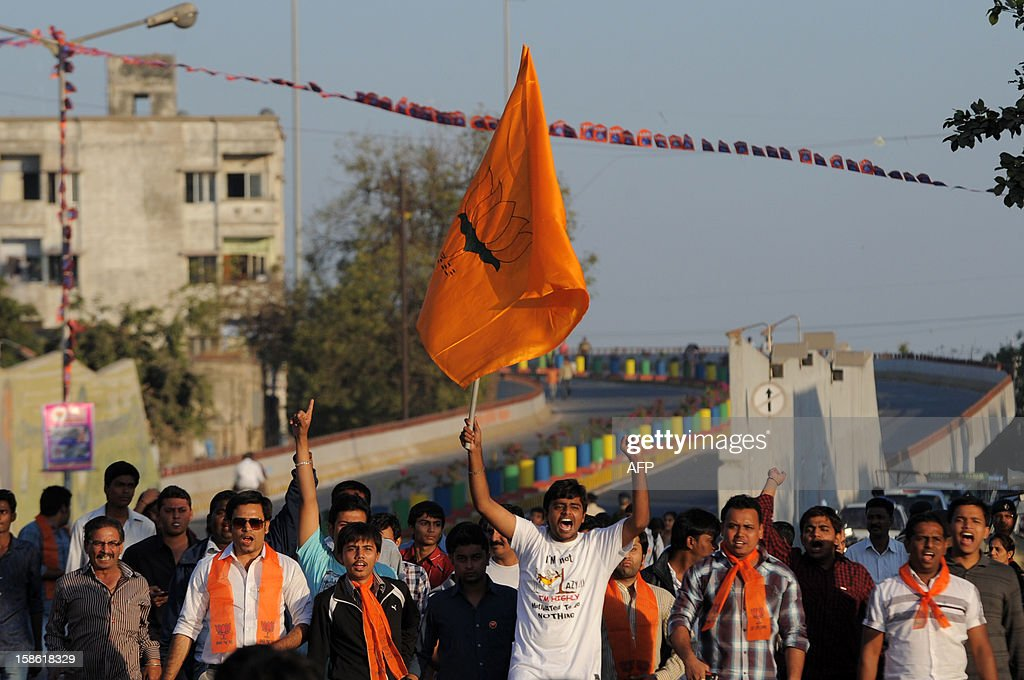 A Bharatiya Janta Party (BJP) supporter displays the BJP flag as he arrives with others to participate in a rally addressed by Chief Minister of the western Indian state of Gujarat Narendra Modi in Ahmedabad on December 21, 2012, after his victory in state assembly elections. Indian Hindu nationalist Narendra Modi should be in a strong position to run for prime minister in 2014 after winning state polls but his own party may act to stop him, newspapers said. Modi, a hardline leader of the right-wing Bharatiya Janata Party (BJP), recorded a thumping victory in his home state of Gujarat to remain as chief minister, triggering renewed speculation about his national ambitions. AFP PHOTO/Sam PANTHAKY