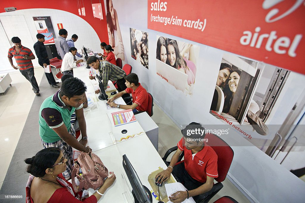 Bharti Airtel Ltd. sales assistants serve customers at the company's flagship store in Mumbai, India on Thursday, May 2, 2013. Bharti Airtel, India's largest mobile-phone operator, posted profit that missed analyst estimates after a weaker rupee raised the interest payments and prices for network equipment. Photographer: Kuni Takahashi/Bloomberg via Getty Images
