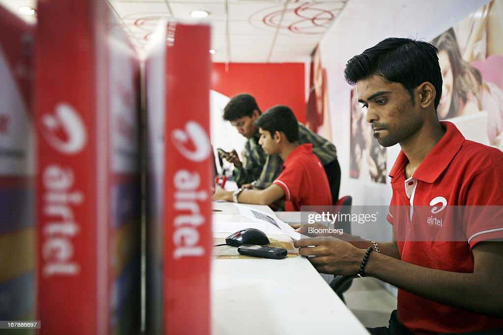 Bharti Airtel Ltd. sales assistants serve customers at the company's flagship store in Mumbai, India on Thursday, May 2, 2013. Bharti Airtel Ltd., India's largest mobile-phone operator, posted profit that missed analyst estimates after a weaker rupee raised the interest payments and prices for network equipment. Photographer: Kuni Takahashi/Bloomberg via Getty Images