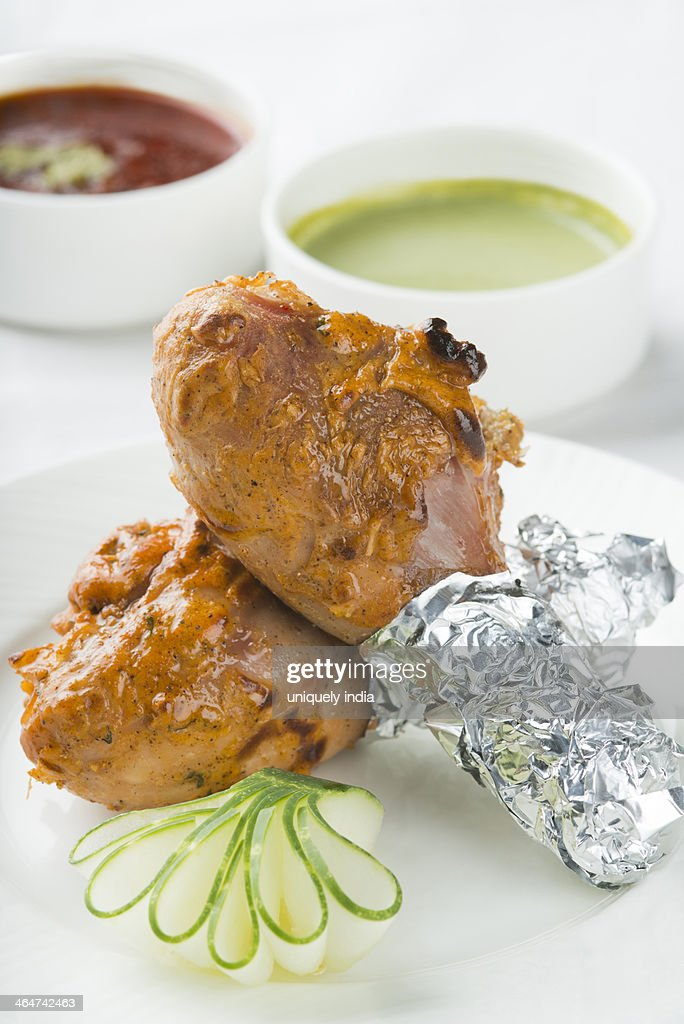 Bharwan Tangri Chicken served in a plate with sauce : Stock Photo