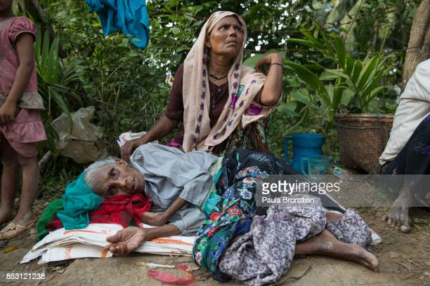 Bhelua Khatun age 70 exhausted from his journey rests on the side of the road as his daughter Anwara 45 looks for humanitarian aid after a new wave...