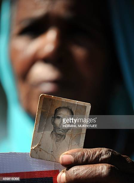 A Bhopal Gas disaster victim holds a frayed photograph of her late husband during a protest rally in Bhopal on December 2 2014 The Bhopal industrial...