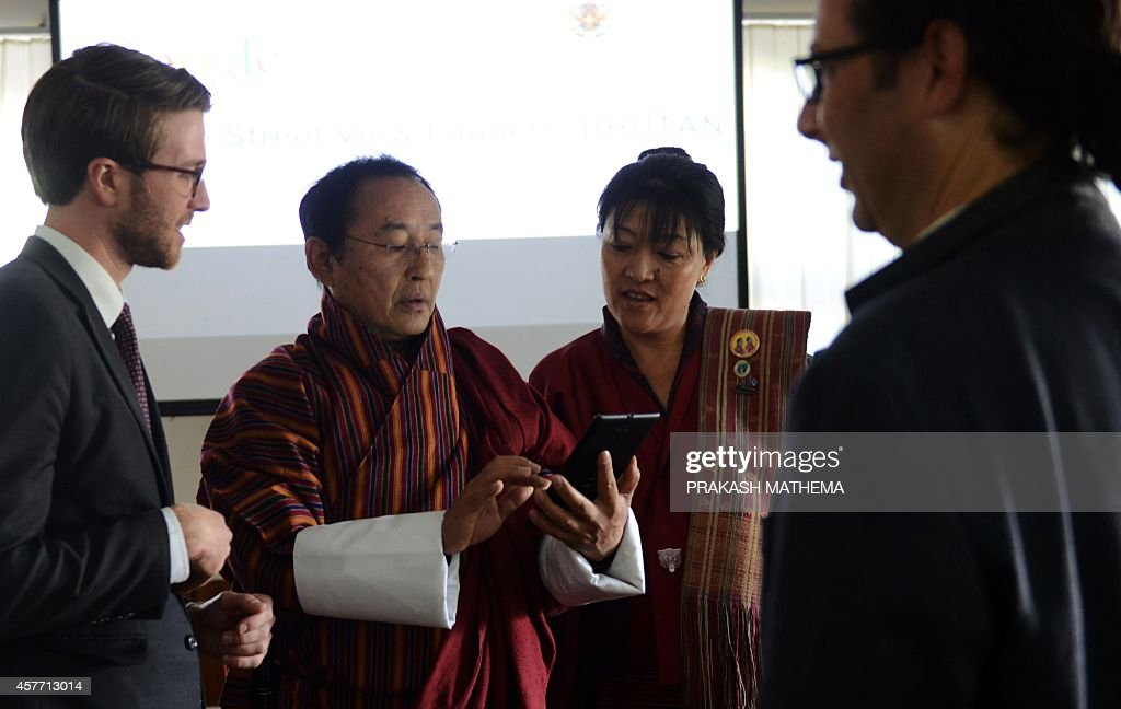 Bhutan Information and Communication Secretary Dasho Kinley Dorji looks at a tablet computer as Director of the Bhutan Tourism Council Chhimmy Pen...
