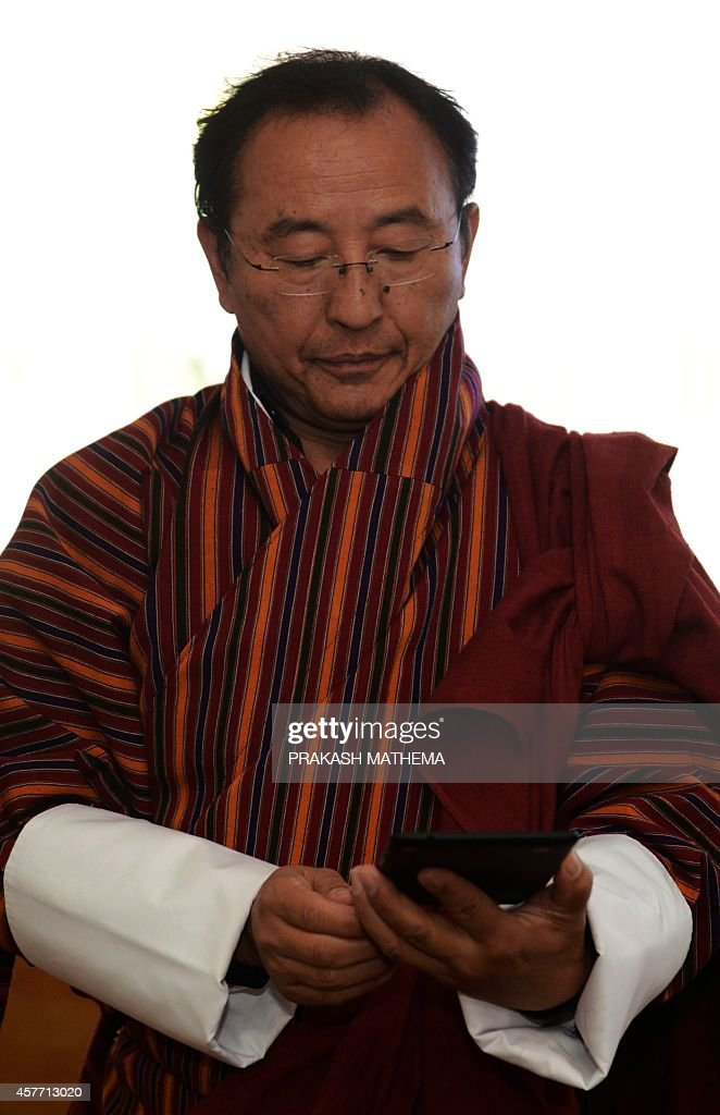 Bhutan Information and Communication Secretary Dasho Kinley Dorji looks at a tablet computer during the launch of the Google Maps Street View project...