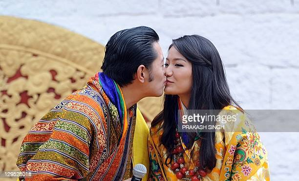 Bhutanese royal couple King Jigme Khesar Namgyel Wangchuck kisses the Queen Jetsun Pema during a ceremony at the main stadium in Thimphu in Bhutan on...