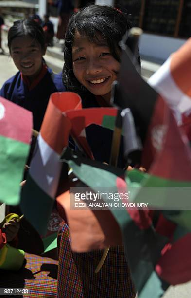 A Bhutanese student distributes regional national flags as youth line up to welcome attendants arriving for the 16th SAARC summit in Thimphu on April...