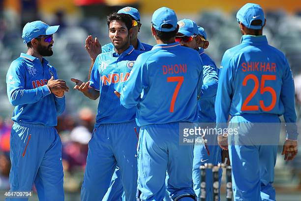 Bhuvneshwar Kumar of India celebrates with team mates after dismissing Amjad Javed of the UAE during the 2015 ICC Cricket World Cup match between...