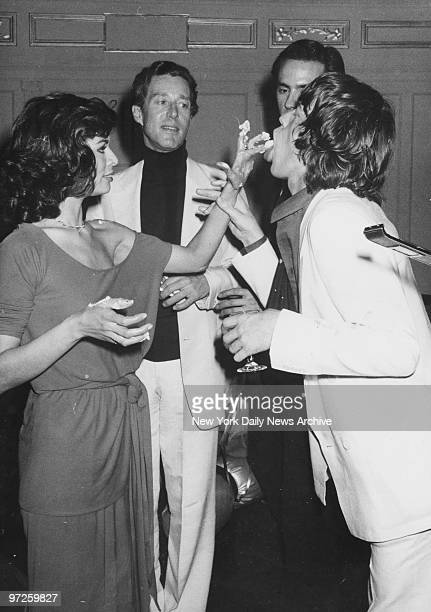 Bianca Jagger feeds cake to husband Mick Jagger as designer Halston looks on during Bianca's birthday bash at Studio 54