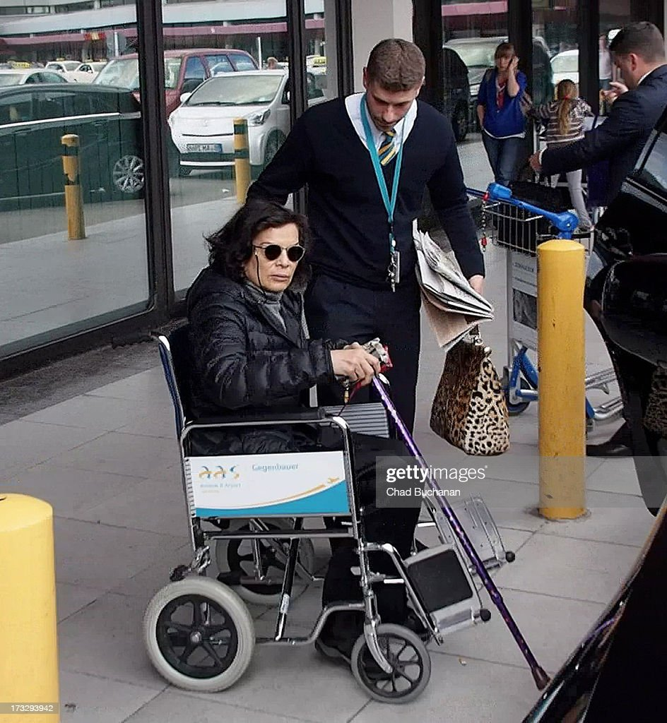 Bianca Jagger is helped out of a wheelchair as she arrives at Tegel Airport on July 11, 2013 in Berlin, Germany.
