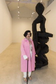 Bianca Jagger poses by 'Yellow Song 2013' a monumental bronze sculpture by artist Georg Baselitz during the Georg Baselitz exhibition preview and...