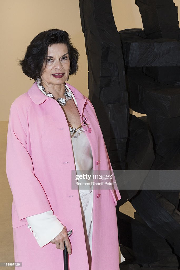 Bianca Jagger poses by 'Yellow Song, 2013', a monumental bronze sculpture by artist Georg Baselitz, during the Georg Baselitz exhibition preview and dinner at Thaddeus Ropac Gallery on September 7, 2013 in Pantin, east of Paris, France. The exhibition opens on September 8.