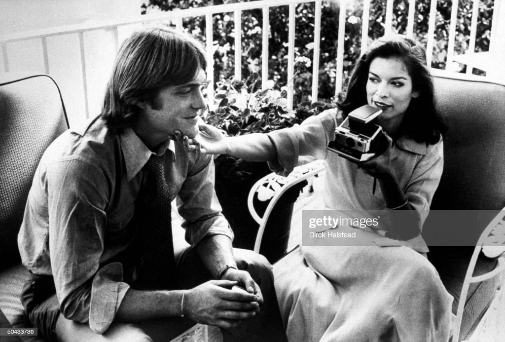Bianca Jagger wife of rock star sitting next to Jack Ford the son of Pres Ford as she holds his chin while preparing to take a snapshot w the...