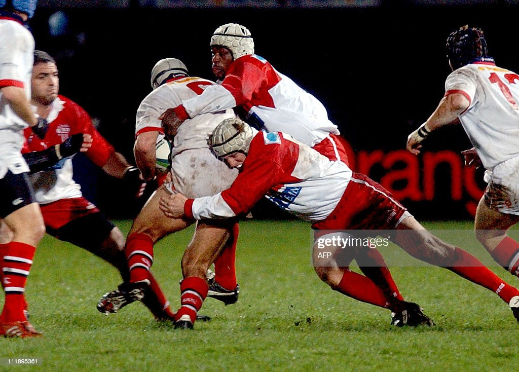 Biarritz tackles fly in on Ulster's Warren Brosnihan during the UlsterBiarritz match at Ravenhill in the Heineken Cup 06 December 2002