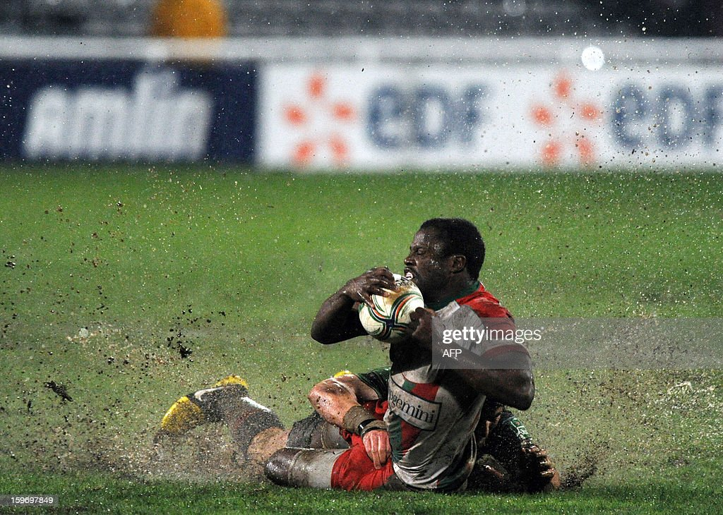 Biarritz's US winger Takudzwa Ngwenya (foreground) is tackled by Harlequins's center George Lowe (hidden) during the European Cup rugby Union match Biarritz Olympique vs Harlequins at the Aguilera stadium in Biarritz, southwestern France, on January 18, 2013.