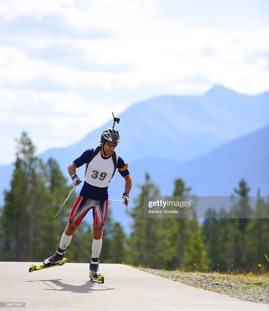 Biathalon racer trains in summer, on roller skiis : Stock Photo