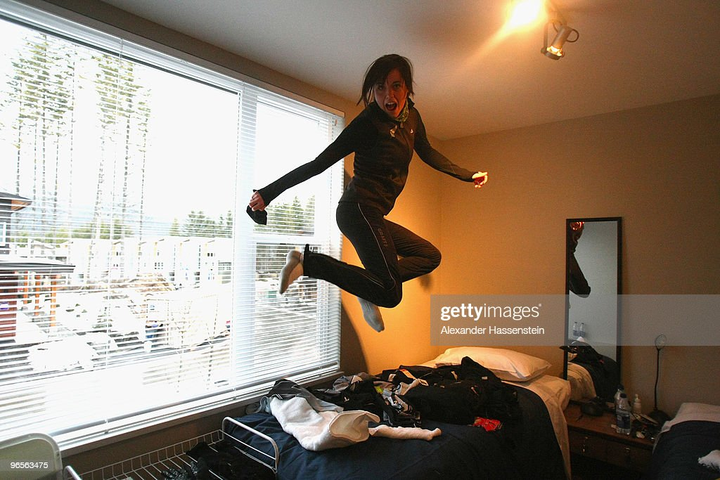 Biathlon athlete Sarah Murphy of New Zealand jumps on her bed at her suite at the Whistler Olympic village during the media tour ahead of the...