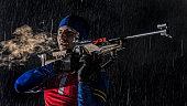 Biathlon competitor preparing for target shooting at night