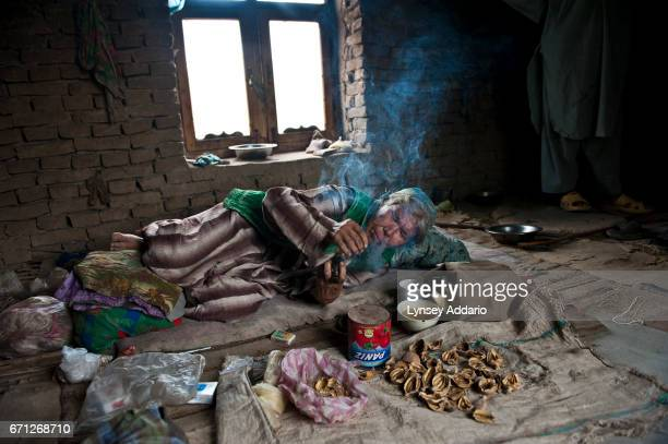 Bibi about 60 years old sits with empty pods of opium as she scrounges for drugs to smoke at home in Shortepa district outside of Mazar e Sharif in...