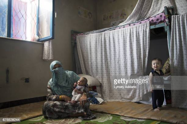Bibi Shireen about 40 sits in her prison cell holding the infant of another cellmate in the Badam Bagh women's prison in Kabul Afghanistan September...