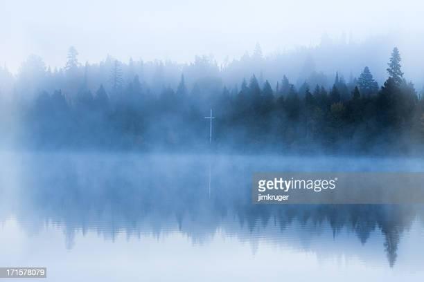 Bible camp cross on foggy shore