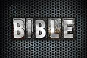 "The word ""Bible"" written in vintage metal letterpress type on a black industrial grid background."