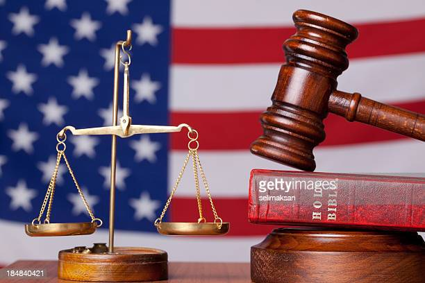 Bible, gavel and scales of justice on american flag background