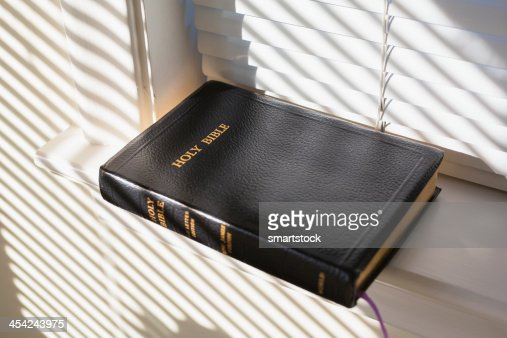 Bible lying on window seal in a home : Stock Photo